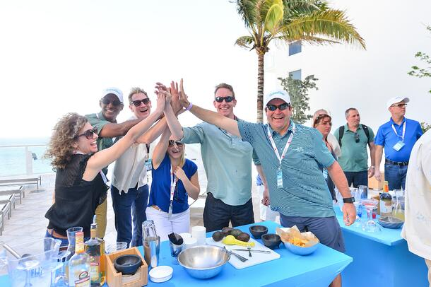 Attendees of RestaurantSpaces 2017 cheer each other on at a cooking competition.