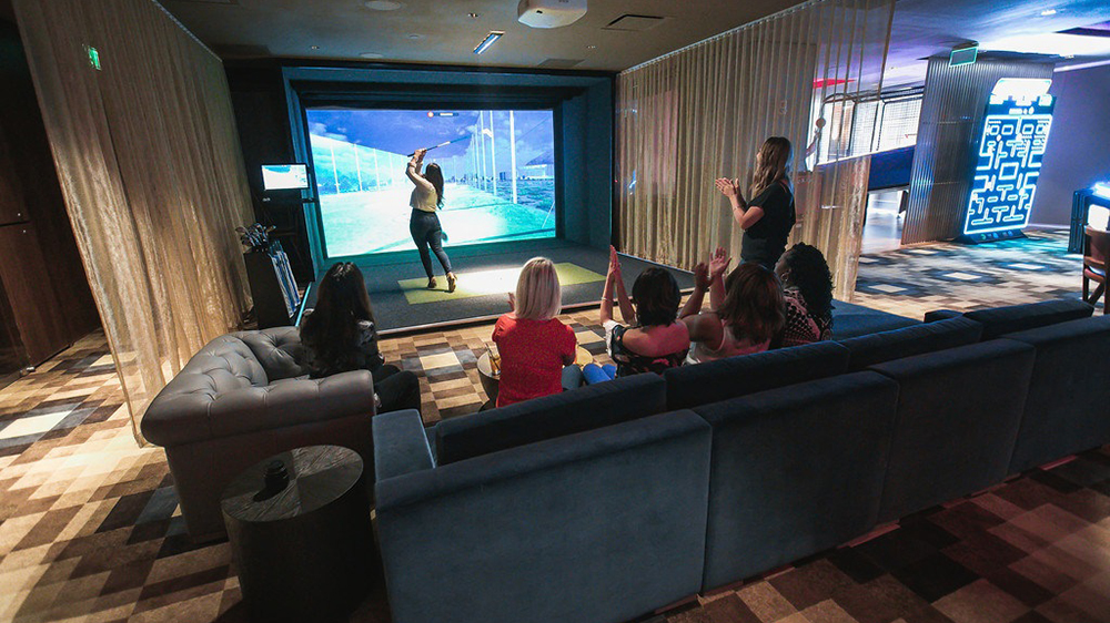 At Topgolf Swing Suite guests hit golf balls at a wall-mounted simulator